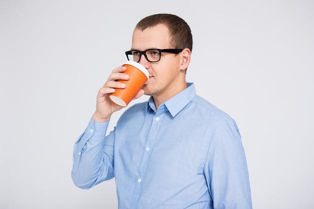 Portrait de jeune homme d'affaires buvant du café ou du thé sur fond gris