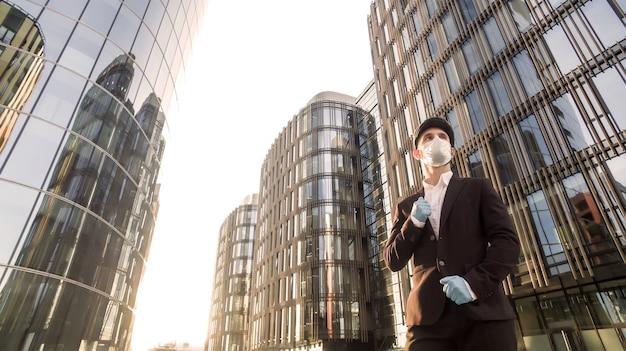 Portrait de jeune homme d'affaires confiant dans un masque médical et des gants en caoutchouc