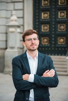 Portrait de jeune homme d'affaires confiant avec ses bras croisés