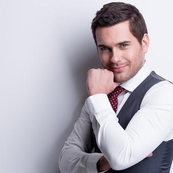 Portrait de jeune homme d'affaires en costume gris avec la main près du visage pose sur le mur.