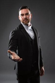 Portrait d'un jeune homme d'affaires en costume tendant la main pour une poignée de main.