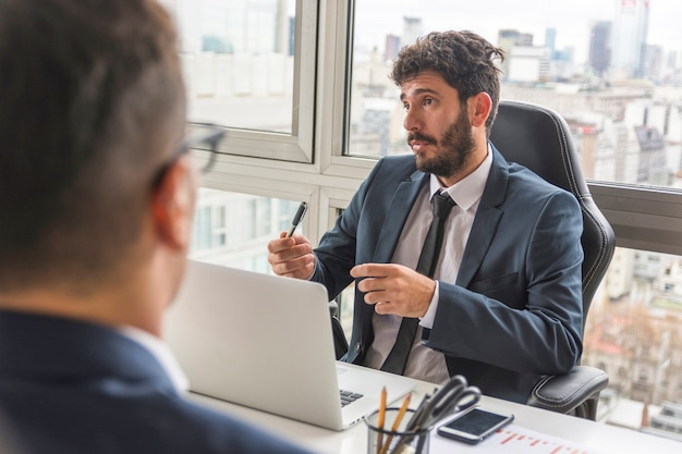 Portrait de jeune homme d'affaires discutant avec son collègue