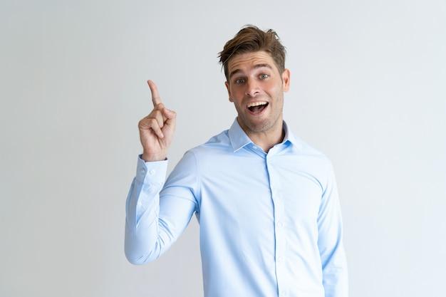 Portrait de jeune homme d'affaires excité ayant idée