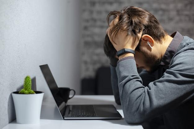Portrait de jeune homme d'affaires frustré tenant la main sur sa tête, assis près d'un bureau avec ordinateur portable, tasse à café et cactus. porter une montre intelligente et des écouteurs sans fil.