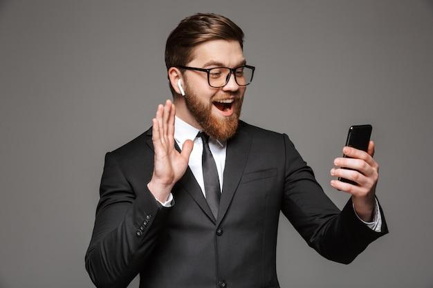 Portrait d'un jeune homme d'affaires heureux dans les écouteurs