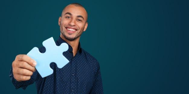 Portrait d'un jeune homme d'affaires heureux tenant un puzzle