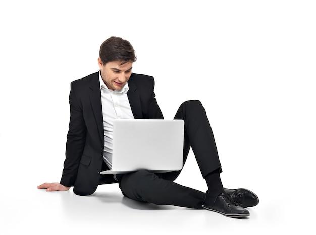 Portrait de jeune homme d'affaires heureux travaillant sur ordinateur portable isolé sur blanc.