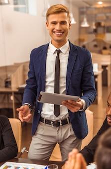 Portrait d'un jeune homme d'affaires lors d'une conférence au bureau.