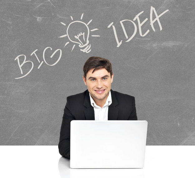 Portrait de jeune homme d'affaires avec ordinateur portable et croquis d'idée derrière l'homme