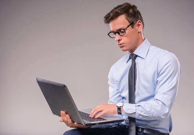 Portrait d'un jeune homme d'affaires avec un ordinateur portable.
