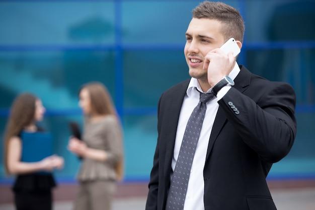 Portrait de jeune homme d'affaires parlant au téléphone en plein air