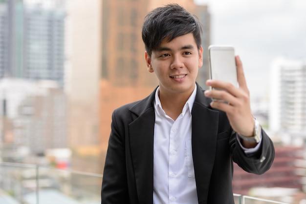 Portrait de jeune homme d'affaires philippin beau contre vue sur la ville en plein air