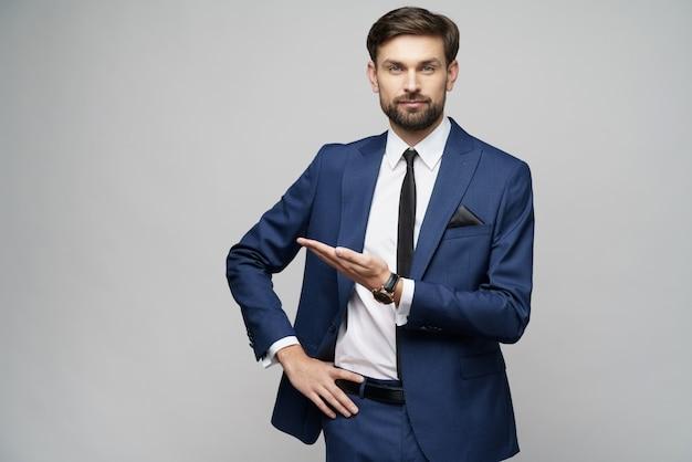 Portrait d'un jeune homme d'affaires pointant sur un espace vide avec son doigt