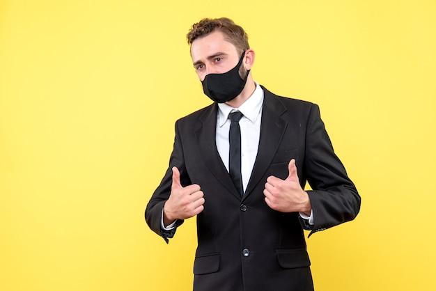 Portrait de jeune homme d'affaires avec le pouce en l'air signe sur jaune