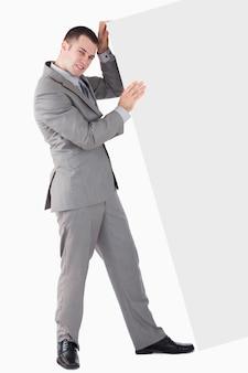 Portrait De Jeune Homme D'affaires En Poussant Un Panneau Vierge Photo Premium
