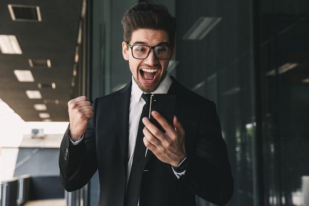 Portrait de jeune homme d'affaires prospère habillé en costume formel debout à l'extérieur du bâtiment en verre et tenant un téléphone mobile