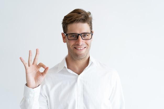Portrait de jeune homme d'affaires prospère montrant le signe ok