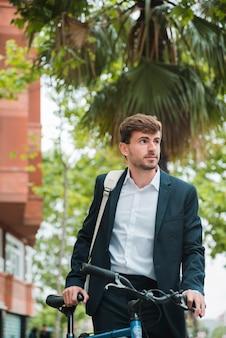 Portrait d'un jeune homme d'affaires avec sa bicyclette à la recherche de suite