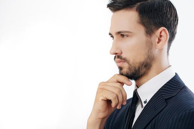 Portrait de jeune homme d'affaires sérieux songeur touchant le menton et regardant en face de lui, isolé sur blanc