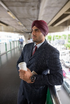Portrait de jeune homme d'affaires sikh indien beau portant turban tout en explorant la ville de bangkok, thaïlande