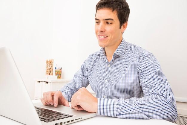 Portrait d'un jeune homme d'affaires souriant à l'aide d'un ordinateur portable sur un tableau blanc