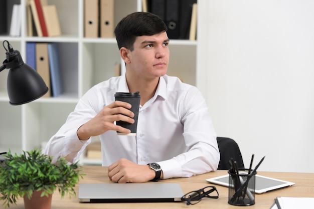 Portrait d'un jeune homme d'affaires tenant une tasse de café jetable dans la main au bureau