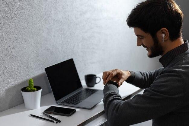 Portrait de jeune homme d'affaires vérifie l'heure sur smartwatch, à l'aide d'écouteurs sans fil