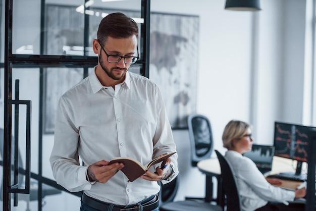 Portrait de jeune homme d'affaires en vêtements formels qui se tient au bureau.
