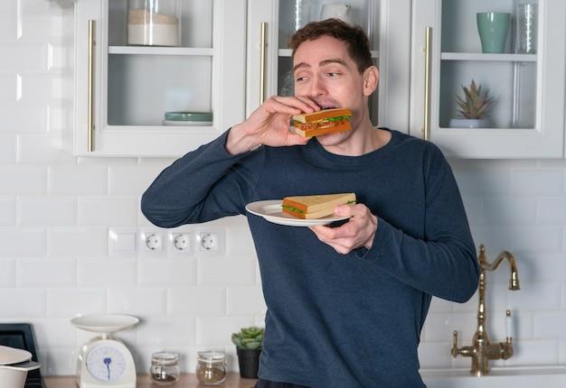 Portrait de jeune homme affamé en pyjama mange de délicieux sandwichs mordant des hamburgers à la maison à