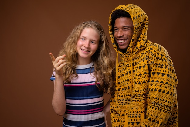 Portrait de jeune homme africain et adolescente caucasienne souriant
