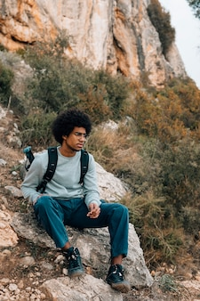 Portrait de jeune homme africain assis sur la montagne
