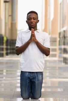 Portrait de jeune homme africain au bâtiment moderne dans la ville en plein air
