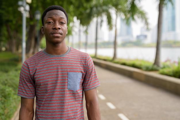 Portrait de jeune homme africain beau se détendre dans le parc