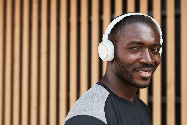 Portrait d'un jeune homme africain dans des écouteurs sans fil souriant à la caméra en marchant dans la ville