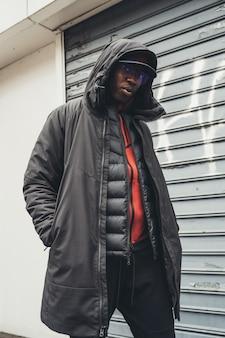 Portrait de jeune homme africain debout dans la rue et à la recherche de caméra