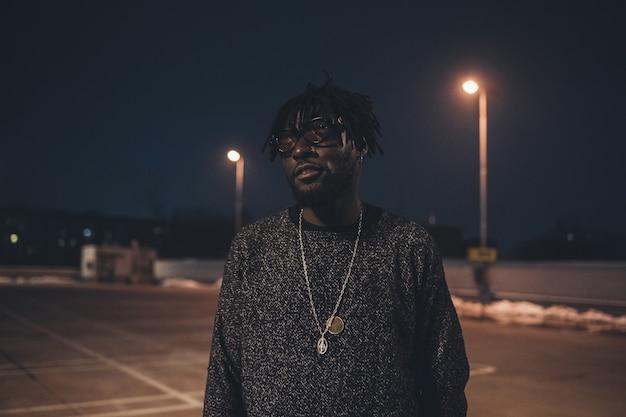 Portrait de jeune homme africain debout en plein air