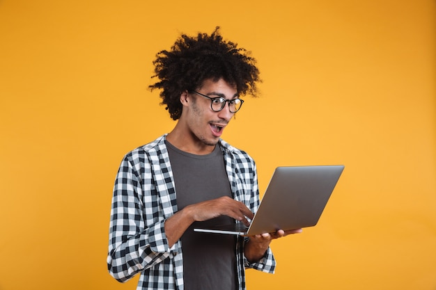 Portrait d'un jeune homme africain excité à lunettes