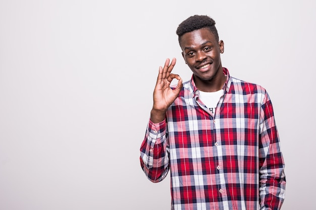 Portrait d'un jeune homme africain heureux en chemise blanche montrant le geste ok isolé