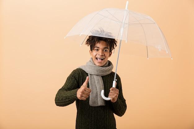 Portrait d'un jeune homme africain heureux habillé en pull et écharpe isolé sur un mur beige, debout sous un parapluie, donnant les pouces vers le haut