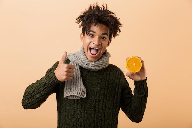 Portrait d'un jeune homme africain heureux habillé en vêtements d'automne isolé sur mur beige, montrant des capsules de pilules et la moitié d'une orange, pouces vers le haut