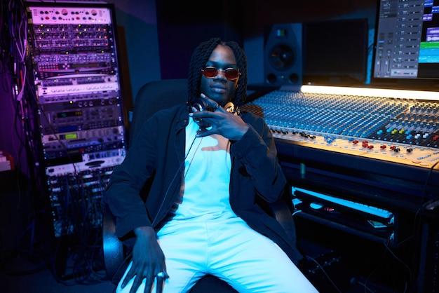 Portrait de jeune homme africain à lunettes de soleil assis dans le studio de musique avec clavier musical en arrière-plan