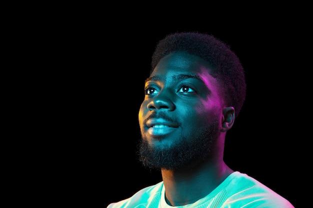 Portrait de jeune homme africain sur mur sombre. concept d'expression faciale des émotions humaines