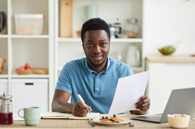Portrait de jeune homme africain planifier sa journée et prendre des notes dans le bloc-notes alors qu'il était assis à la table dans la cuisine