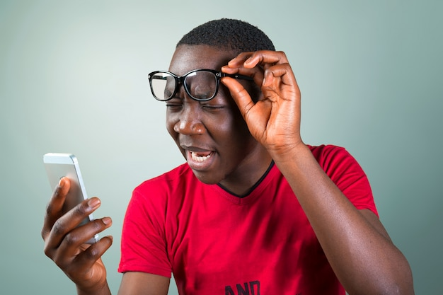 Portrait d'un jeune homme africain souriant à l'aide de smartphone