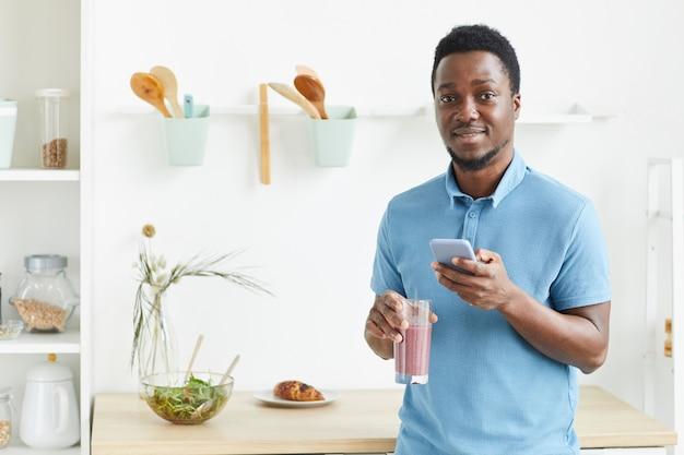 Portrait de jeune homme africain souriant et buvant un cocktail frais le matin à la maison