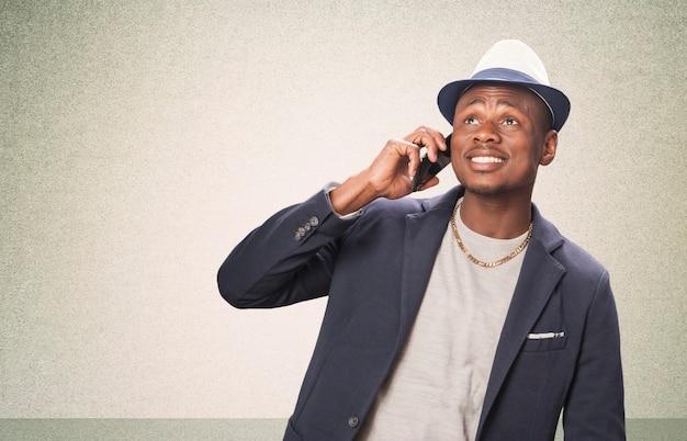 Portrait de jeune homme africain surpris regardant un téléphone portable
