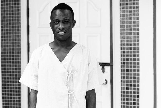 Portrait de jeune homme africain en tant que patient de l'hôpital à l'extérieur en noir et blanc