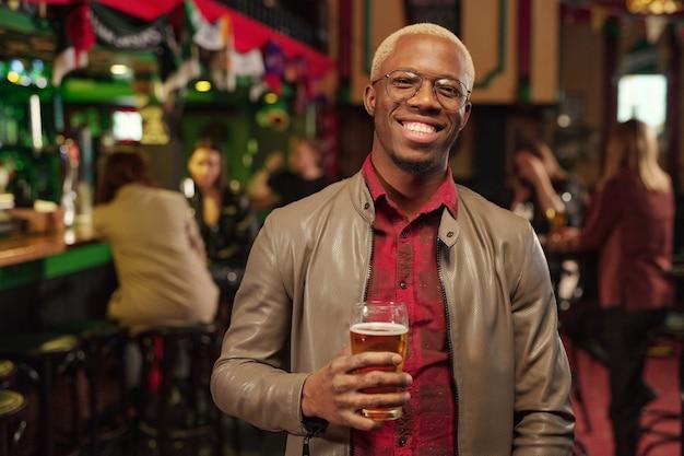 Portrait de jeune homme africain tenant un verre de bière et souriant à la caméra en se tenant debout dans le bar