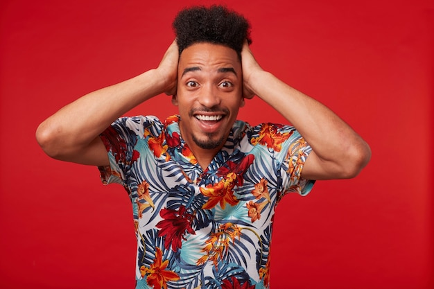 Portrait de jeune homme afro-américain en chemise hawaïenne, a l'air étonné et heureux, se dresse sur fond rouge et tient sa tête.