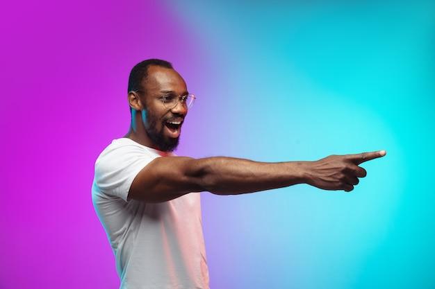 Portrait de jeune homme afro-américain sur fond de studio dégradé en néon. beau modèle masculin dans un style décontracté, chemise blanche. concept d'émotions humaines, d'expression faciale, de ventes, d'annonces.